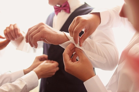 hand cuff: Hands helping the groom with buttons