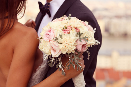Detail einer Braut und Bräutigam umarmend. Braut hält schöne Hochzeitsstrauß Lizenzfreie Bilder