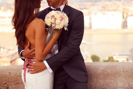 Detail van een bruid en bruidegom omarmen. Bruid die het mooie bruidsboeket Stockfoto