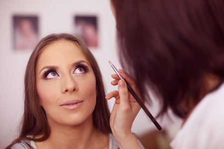 make up artist: Make up artist applying make up on woman face Stock Photo