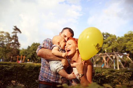 Happy family playing with yellow balloon