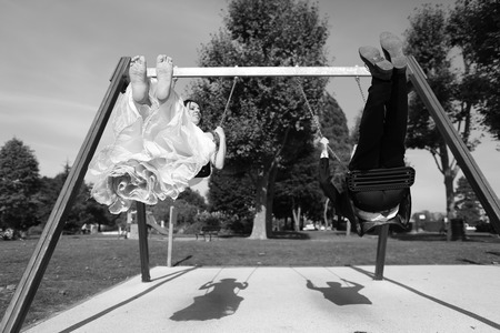 swing set: Bride and groom playing on a swing set