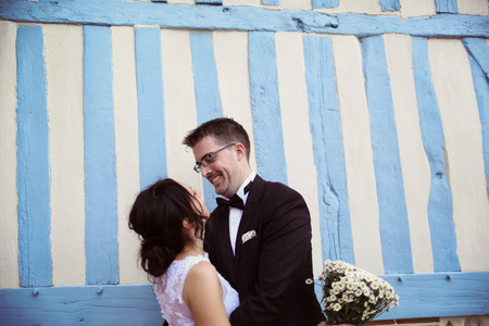 honeymoon suite: Lovely bride and groom at a blue and white striped wall