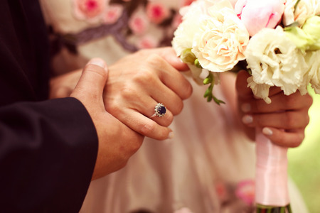 arm bouquet: Bride and groom holdin hands. Bride holding beautiful wedding bouquet Stock Photo