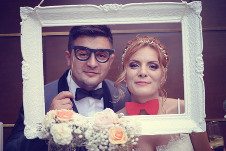 Funny bride and groom in a white frame
