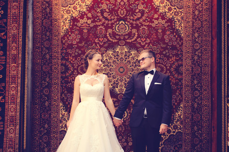 Braut und Bräutigam vor einem hängenden Teppich