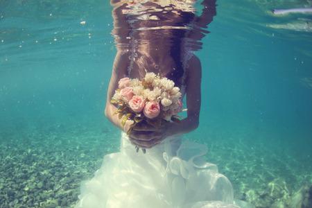 Handen van een bruid bedrijf bruiloft boeket onderwater