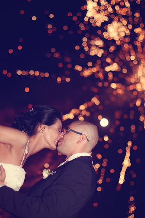 fire crackers: Bride and groom surrounded by fire crackers Stock Photo