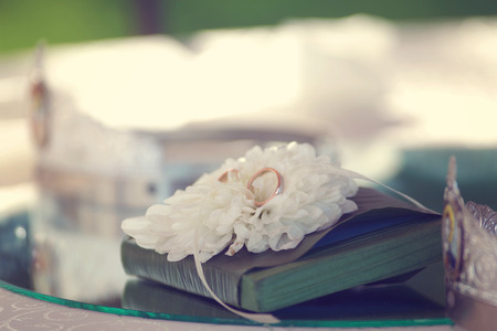 white pillow: Gold wedding ring on white flower