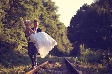 Bruidegom die zijn bruid op een spoorweg Stockfoto
