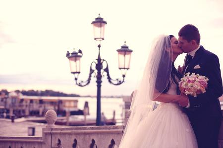street lights: Bride and groom kissing near street lights