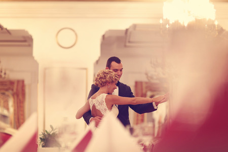 butonniere: Bride and groom dancing in empty restaurant