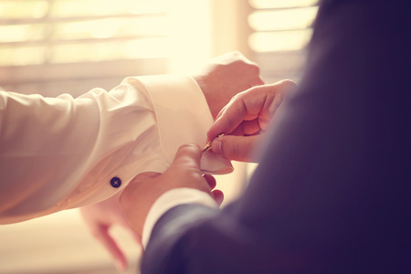 cuff link: Groomsman helping the groom
