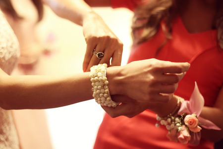 bridesmaid: Bridesmaid putting bracelet on bride Stock Photo