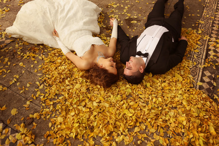Bride and groom laying on autumn leaves Stock Photo