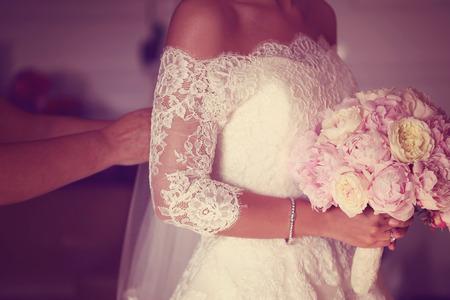 Hände einer Braut mit Pfingstrosen Blumenstrauß