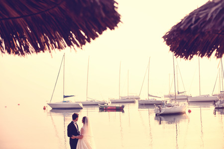 trash the dress: Bride and groom near water