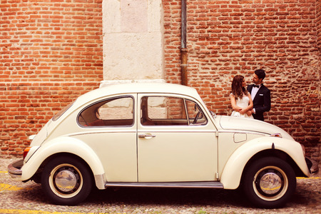 Bruid en bruidegom in de buurt van oldtimers