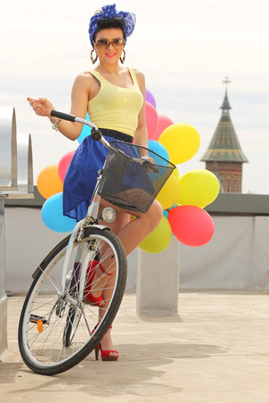baloons: beautiful brunette with baloons on bicycle Stock Photo