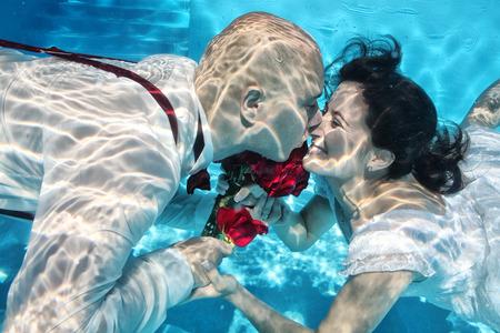 Bruid en bruidegom kussen onder water bruiloft duiken rode bloemen