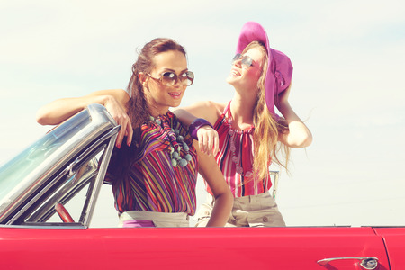 cars on the road: Beautiful ladies with sun glasses posing in a vintage retro car