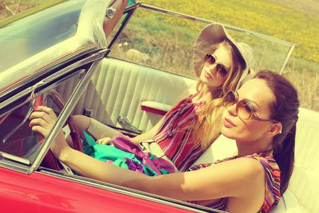 Schöne Frauen, die ein rotes Auto Retro-Vintage tragen accesoriess Fahr