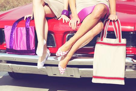 happy asian people: Beautiful ladies legs posing in a vintage retro car Stock Photo