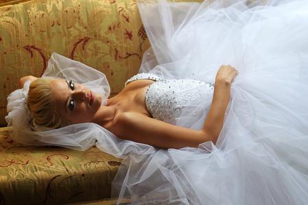 honeymoon suite: Beautiful bride on sofa Stock Photo