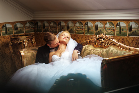 man in suite: Bride and groom on a luxury hotel, kissing on a sofa Stock Photo