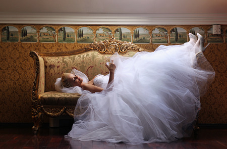 Extravagant bride on sofa, holding a glass of wine