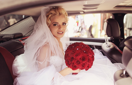 white backing: Beautiful bride smile in a luxury car with red rose flower bouquet