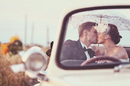 Bruid en bruidegom in een oldtimer