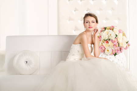 Wunderschöne Braut mit weißen Kleid mit Blumen Bouquet