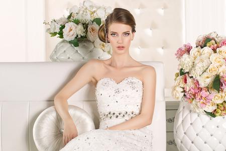 Prachtige bruid met witte jurk met bloemen boeket