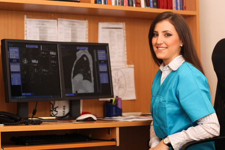 women s health: Portrait of a smiling female doctor sitting at work desk