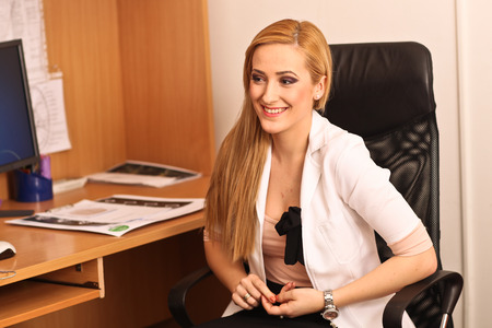 women s health: female doctor sitting at her work desk and smiling