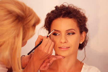 Young beautiful bride applying wedding make-up by make-up artist