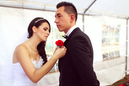 corsage: Bride putting rose corsage on grooms chest