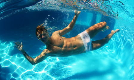 Sexy guy diving in pool underwater