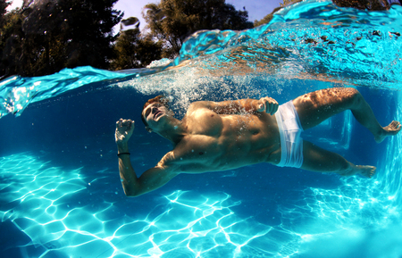 only one man: Sexy guy diving in pool underwater