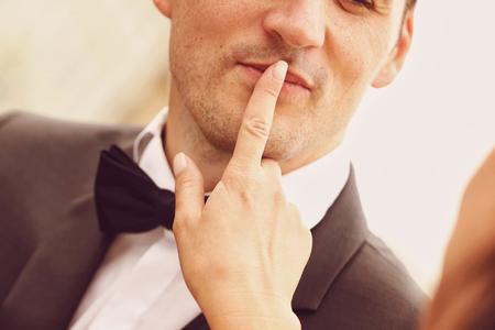 shush: Bride making shush sign with groom