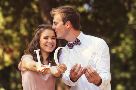 Beautiful bridal couple kissing and holding LOVE letters