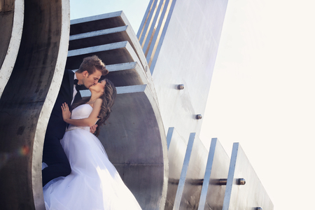 Beautiful bridal couple embracing near architecture