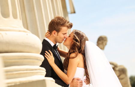 Beautiful bridal couple embracing near columns Imagens