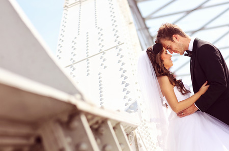 bridal couple: Beautiful bridal couple embracing near architecture