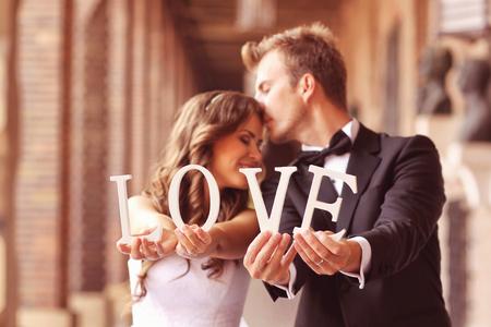 Mooie bruid en bruidegom kussen en houden liefdesbrieven Stockfoto