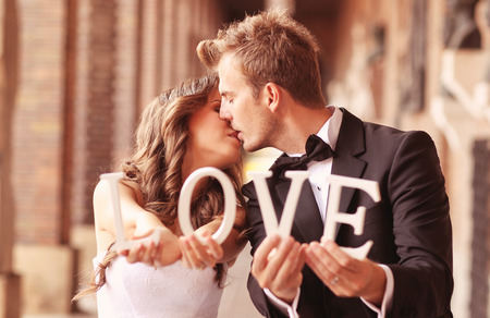 hugging couple: Beautiful bride and groom kissing and holding LOVE letters