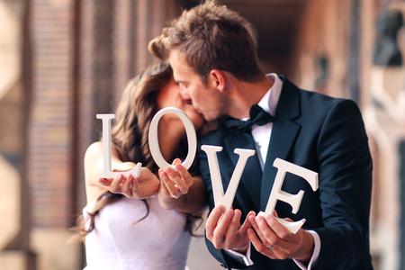 Schöne Braut und Bräutigam küssen und halten Liebesbriefe