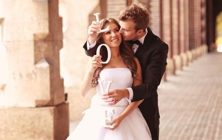 Schöne Braut und Bräutigam umarmt in der Stadt