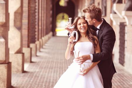 Mooie bruid en bruidegom die in de stad omhelzen Stockfoto